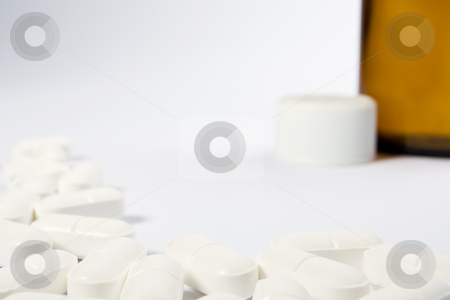 Pill Border with Bottle stock photo, A border of pills on the left-hand side and lower part of a white frame with an opend bottle in the top right-hand area by Steve Smith