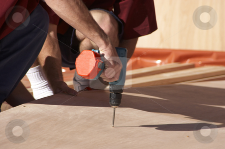 Screwing In stock photo, Workman using a electric drill to put a screw in by Nicholas Rjabow