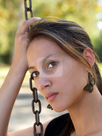 Young asian american woman holding chain from swing stock photo, Young asian american woman outdoor portrait head on chain by Jeff Cleveland