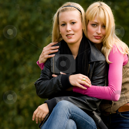 Sisterhug stock photo, Two sisters in a park having fun by Frenk and Danielle Kaufmann