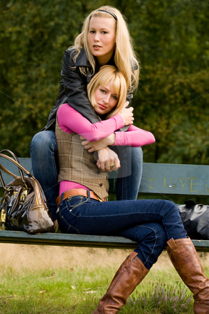 2 sisters on a bench stock photo, Two sisters in a park having fun by Frenk and Danielle Kaufmann