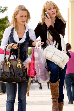 1 girl with a phone stock photo, Two young girls shopping in the sunny weather by Frenk and Danielle Kaufmann