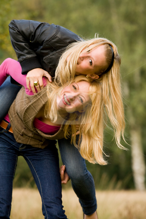 Falling and smiling stock photo, Two sisters in a park having fun by Frenk and Danielle Kaufmann