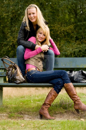 Happy sisters on a bench stock photo, Two sisters in a park having fun by Frenk and Danielle Kaufmann