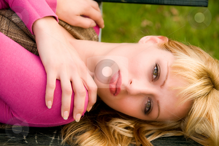 Sweet blond girl on a bench stock photo, Beautifull young girl relaxing in a park by Frenk and Danielle Kaufmann