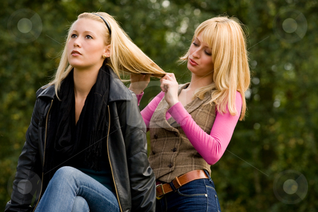 Concentrated on her hair stock photo, Two sisters in a park having fun by Frenk and Danielle Kaufmann