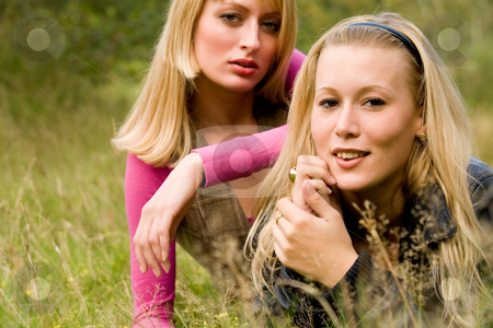 Sisters in the grass stock photo, Two sisters in a park having fun by Frenk and Danielle Kaufmann