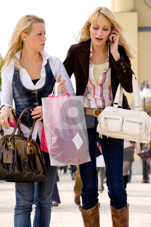 1 girl is calling stock photo, Two young girls shopping in the sunny weather by Frenk and Danielle Kaufmann