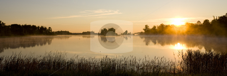 Minnesota Morning stock photo, A minnesota morning as mist rolls off a small still lake. by John McLaird