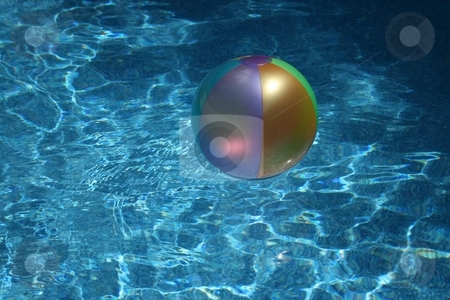 A Summer Day stock photo, A beach ball flaoting in a swimming pool by Jeffrey Newell