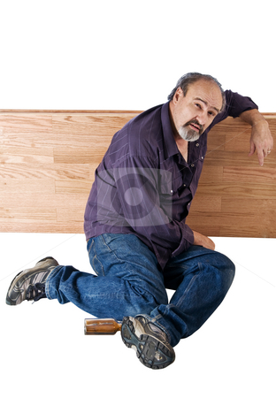 Night in the park for homeless man stock photo, A homeless man leans against a wooden divider as he wakes up. by RCarner Photography