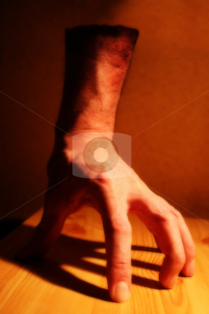 Fantasy Hand stock photo, An effects image of a disembodied hand under tungsten lighting on a wooden board with a heavy shadow. Intentionally semi-blurred. by Steve Smith