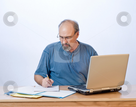 Business man working stock photo, A businessman takes notes from the computer search results. by RCarner Photography
