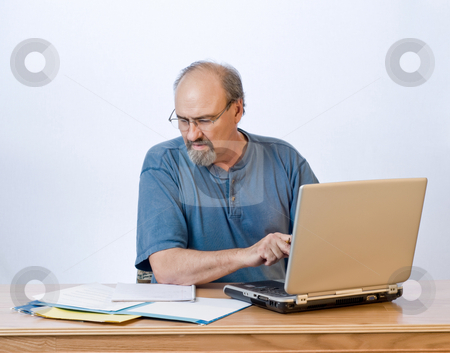 Slow typing businessman stock photo, A businessman transcribes his notes onto the computer. by RCarner Photography