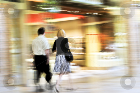 Shopping in a mall stock photo, Couple shopping in a mall, panning shot, intentional in-camera motion blur by Elena Elisseeva