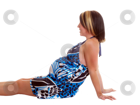 Young pregnant woman on floor in blue dress against isolated background stock photo, Pregnant woman sitting on floor against isolated background by Jeff Cleveland