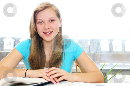 Happy teenage girl studying stock photo, Happy smiling teenage girl studying with textbooks by Elena Elisseeva