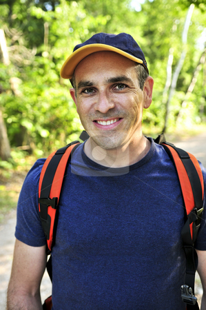 Man hiking on forest trail stock photo, Portrait of happy middle aged man on a forest trail by Elena Elisseeva