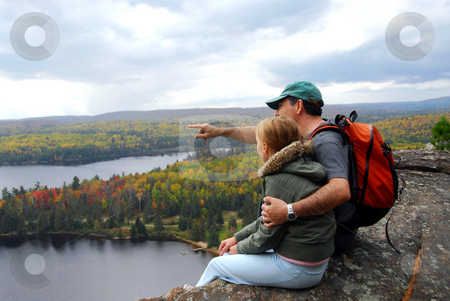 Family hill top stock photo, Parent and child sitting on cliff edge enjoying scenic view by Elena Elisseeva