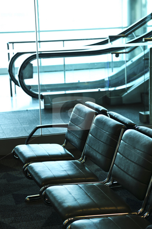 Airport interior stock photo, Row of chairs and escalator inside an airport by Elena Elisseeva
