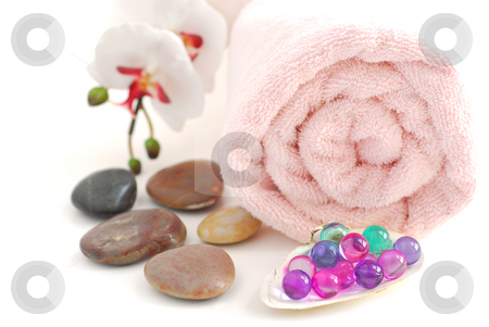 Spa stock photo, Pink rolled up towel with a stack of massage stones and bath beads on white background by Elena Elisseeva