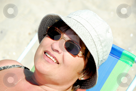 Woman beach stock photo, Mature woman relaxing in a beach chair by Elena Elisseeva