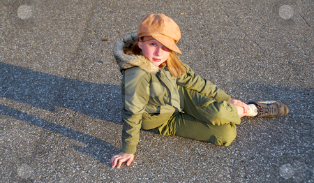 Girl sit outside stock photo, Girl in fall clothes sitting on asphalt pavement by Elena Elisseeva