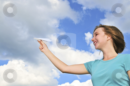 Young girl holding paper airplane stock photo, Young teenage girl holding a paper airplane by Elena Elisseeva