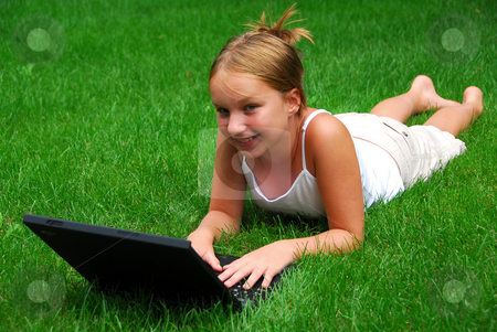 Girl computer stock photo, Young girl lying on grass in a park with laptop computer by Elena Elisseeva