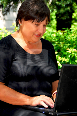 Woman computer stock photo, Mature woman working on laptop computer outdoors by Elena Elisseeva