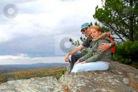 Hikers stock photo, A parent and a child sitting on a cliff edge enjoying scenic view by Elena Elisseeva