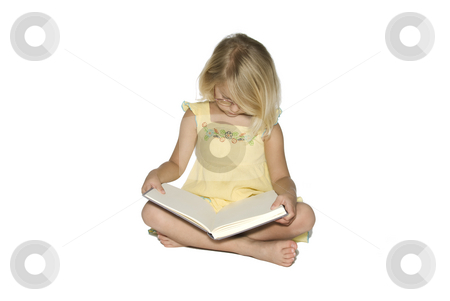 Little Girl Studying Book stock photo, A young blonde girl sitting crosslegged while reading a textbook.  Isolated on a white background by A Cotton Photo