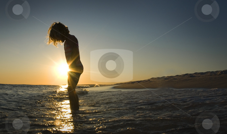 Little Girl Sunset Beach stock photo, A little girl stares at the incoming waves while the sun sets beyond her by A Cotton Photo