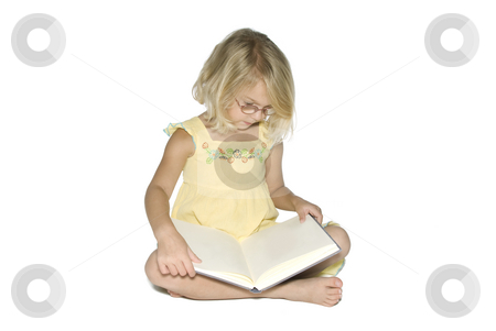 Little Girl with Book stock photo, A young blonde girl sitting crosslegged while reading a textbook.  Isolated on a white background by A Cotton Photo