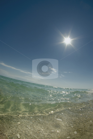 Star Sun Beach stock photo, Fisheye view close to the ground of a calm ocean with the bright sun in the sky on a clear day by A Cotton Photo