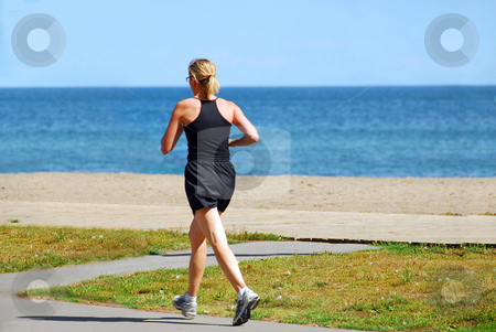 Running woman stock photo, Young woman joggin by sea side in the summer by Elena Elisseeva