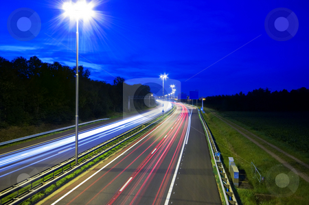 Night highway stock photo, Highway at night with rays of light passing by by Karin Claus