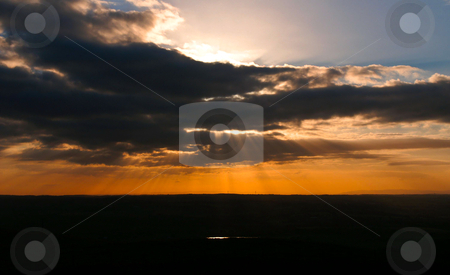 Dramatic sunset stock photo, Dramatic sunset with dark clouds and sunrays by Karin Claus