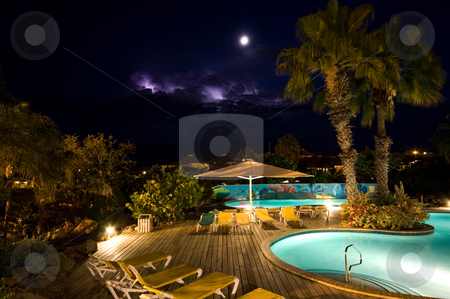 Night pool stock photo, Swimmingpool at night with thunder in the back by Karin Claus