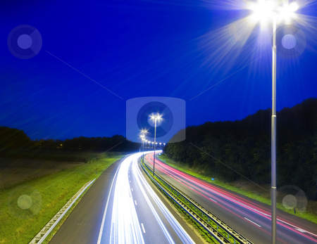 Highway stock photo, High way by night with speeding rays of light from traffic passing by by Karin Claus