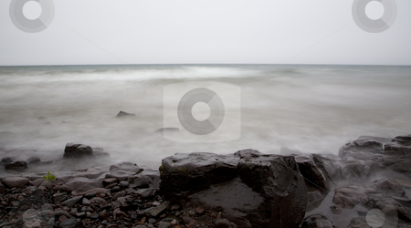 Fog, Mist, Water, and Stone stock photo, Fog, mist, water, and stone on a slow exposure of Lake Superior in Northern Minnesota, by John McLaird
