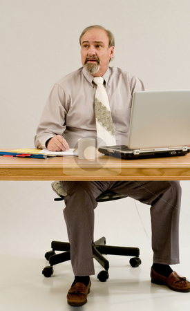 Businessman with emphysema stock photo, A businessman seated at a desk while attatched to an oxygen concentrator. by RCarner Photography