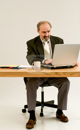 Businessman finishes his report stock photo, Businessman in suit typing on a laptop computer by RCarner Photography