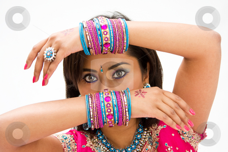Face and hands stock photo, Beautiful face of a Bengali bride with her arms across her head covered with colorful bracelets, isolated by Paul Hakimata