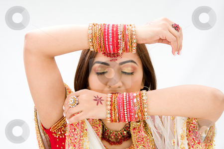 Face and hands stock photo, Beautiful face of a Bengali bride with her arms across her head covered with colorful bracelets and eyes closed, isolated by Paul Hakimata