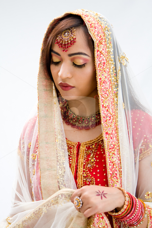 Elegant Bengali bride stock photo, Elegant Bengali bride arranging veil looking down, isolated by Paul Hakimata
