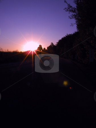Sunrise bicycling stock photo, A bicyclist riding into the sunrise, near Back Bay in Newport Beach CA. by Rob Wright
