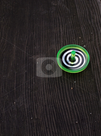 Green Spinning Top stock photo, Green, white, and black swirly spinning top on a wooden background by Julie Bentz