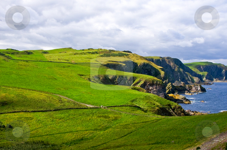 Dangrous cliffs  stock photo, Dangerous coastal cliffs covered with grass and rain clouds in the back by Karin Claus