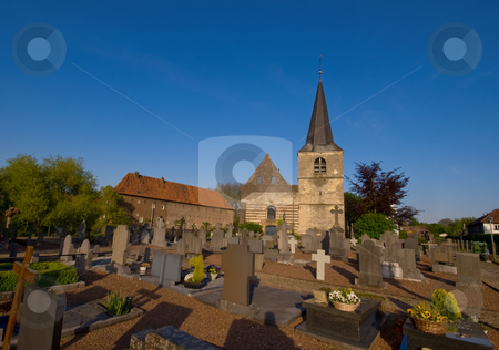 Graveyard on a sunny day  stock photo, Graveyard on a sunny day and blue sky with a little church by Karin Claus